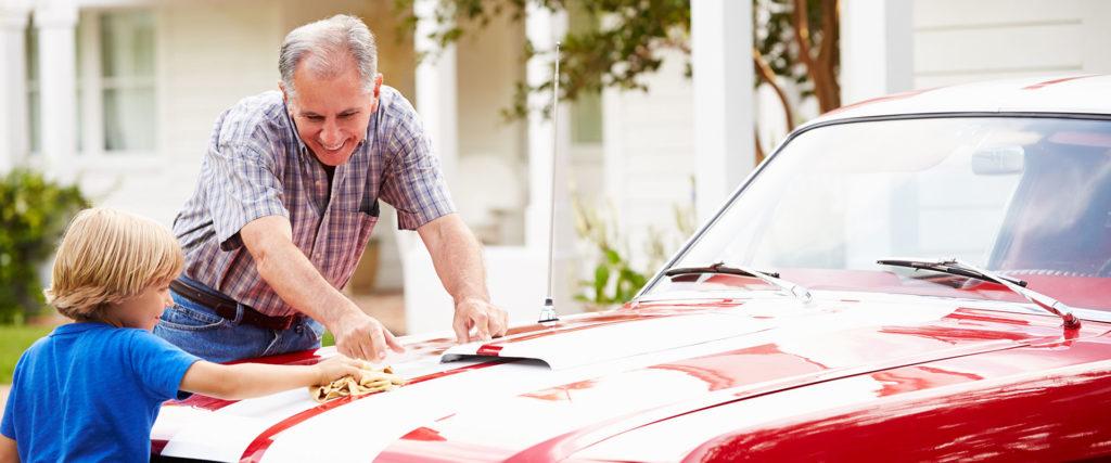 man and grandson washing car
